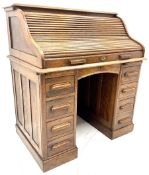Early 20th century oak twin pedestal shaped tambour roll top desk enclosing fitted interior