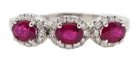 White gold three stone oval ruby and round brilliant cut diamond cluster ring