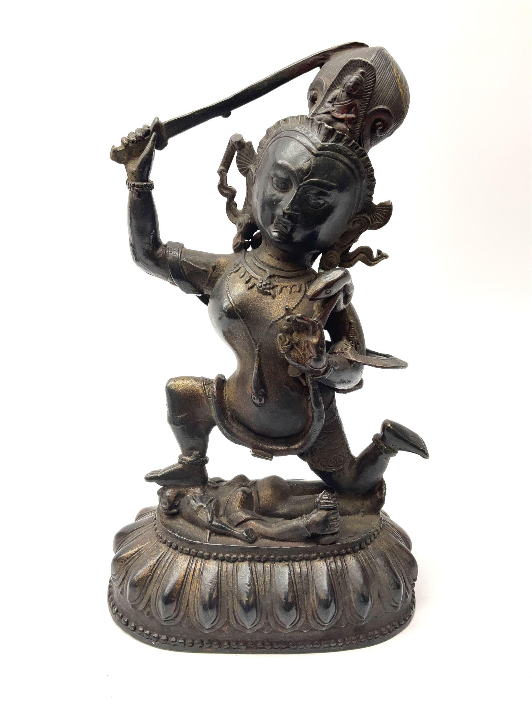 An eastern figure bronzed figure modelled as female deity kneeling upon figure