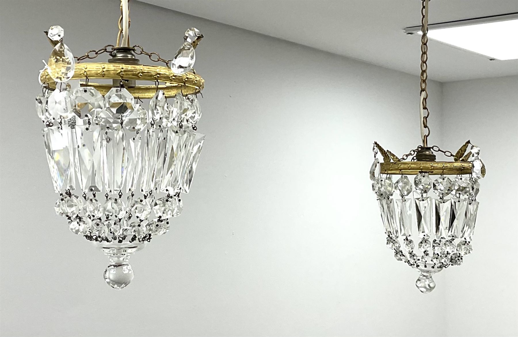 A pair of cut glass bag chandeliers with gilt metal mounts of clear glass drops