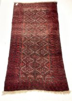 Persian red ground rug with repeating lozenge design