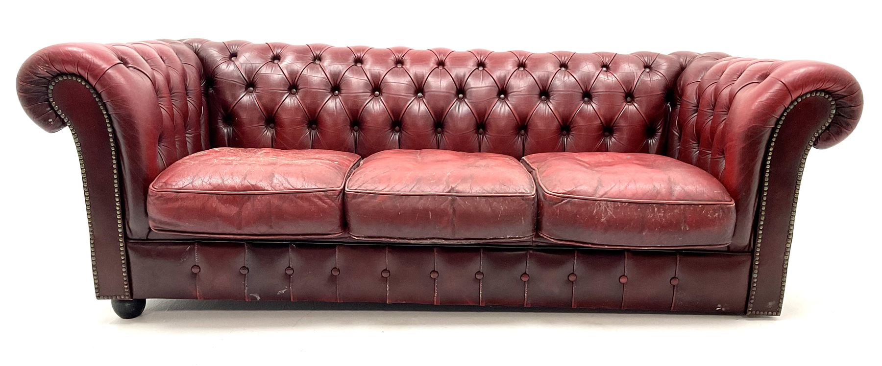 Three seat chesterfield sofa upholstered in deep buttoned ox blood studded leather