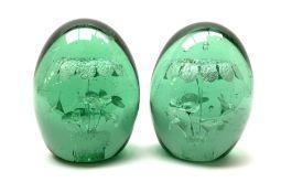 A pair of Victorian green glass dump paperweights