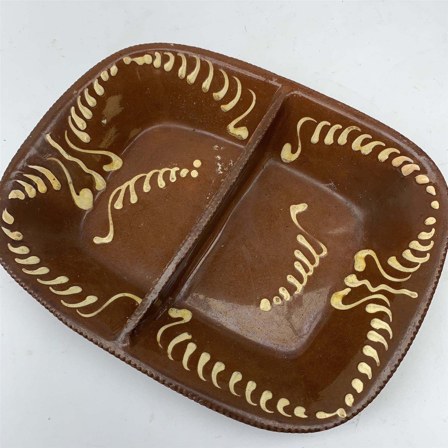 A Victorian terracotta two-division dish of rounded oblong form with cream slipware decoration - Image 2 of 3