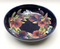A large Moorcroft bowl decorated in the Iris pattern upon a dark blue ground