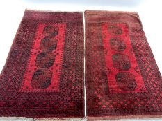Two similar mid 20th century Afghan Bokhara red ground rugs