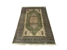 Persian design green and beige ground carpet