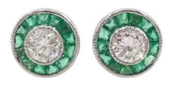 Pair of 18ct white gold round diamond and calibre cut emerald circular stud earrings
