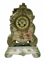 An early 20th century French porcelain clock with rococo scrolling in a cartouche form with gilt hig