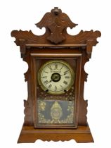 An early 20th century spring driven alarm clock in the style of an American �gingerbread� shelf clo