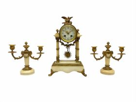 A late 19th century French portico clock with a pair of matching double light candelabra
