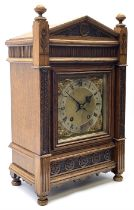A late 19th century German eight-day mantle clock in an oak case striking the quarters and hours on