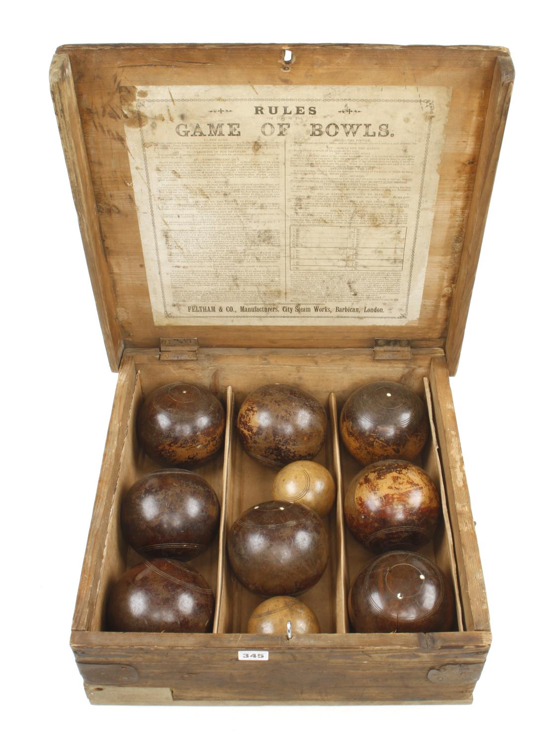 Two sets of lawn bowls in pine box with orig rules the makers label with FELTHAM & Co inside the lid