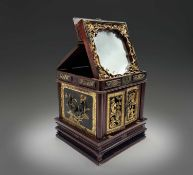 A Chinese hardwood and giltwood carved table cabinet, circa 1900, the hinged cover opening to reveal