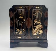 A Japanese gilt and black lacquered table cabinet, early 20th century, the pair of panelled doors