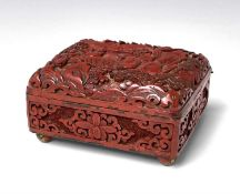 A Chinese cinnabar lacquer box, early 20th century, carved with figures in a landscape, on brass bun
