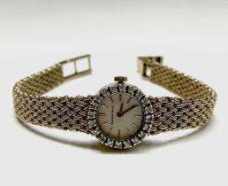 A ladies Bueche-Girod 9ct gold wristwatch with diamond-set bezel with 17 jewel movement,