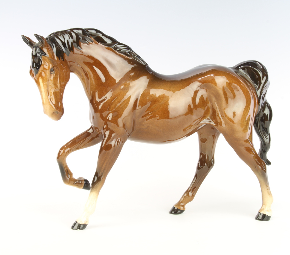 A Royal Doulton figure of a horse with right leg raised, gloss brown, 29cm