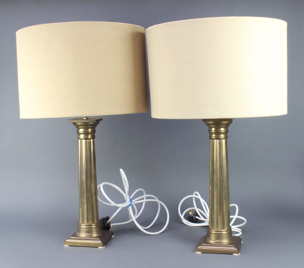 A pair of gilt metal reeded column table lamps with Doric capitals on square bases, complete with