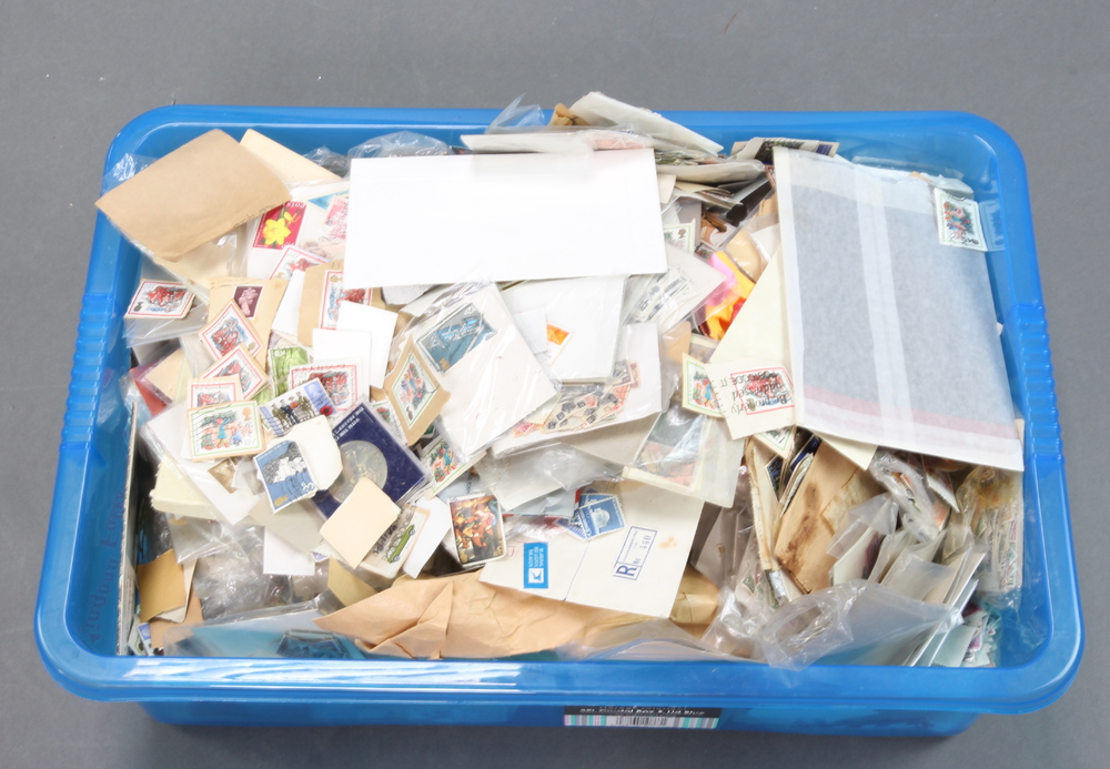 A collection of used world stamps, some on paper, some loose, contained in a large crate
