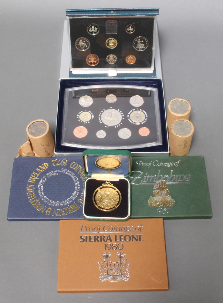 A 2000 commemorative coin set, 4 other cased coin sets, a gilt crown and rolls of commemorative