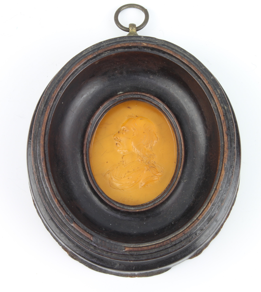 A carved amber oval portrait miniature of Oliver Cromwell dated 1650, signed O B 5.5cm x 4.5cm