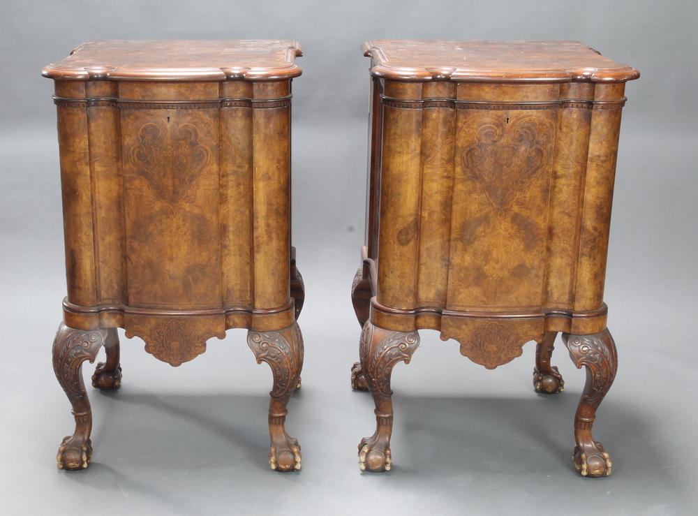 A pair of 19th Century Continental shaped inlaid walnut pedestal cupboards with moulded and dentil