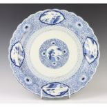 A Chinese blue and white charger with panels of landscape studies 47cm This charger has some contact