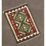 A brown and black ground Maimana Kilim rug with 2 stylised diamonds to the centre 180cm x 58cm
