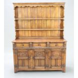 A 17th Century style carved oak dresser, the raised back fitted 2 shelves, base fitted 3 drawers