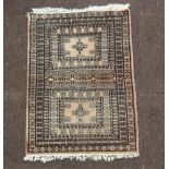 A white and black ground Bokhara rug, 2 panels to the centre within a multirow border 88cm x 62cm