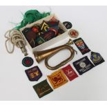 A miniature copper and brass bugle 13cm, a whistle and minor cloth badges