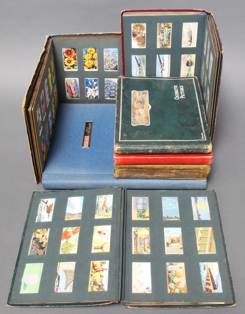 An album containing Kensitas silk cigarette cards together with 6 albums of cigarette cards