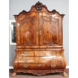 A 19th Century Dutch walnut linen press, the arched upper section heavily carved throughout, the