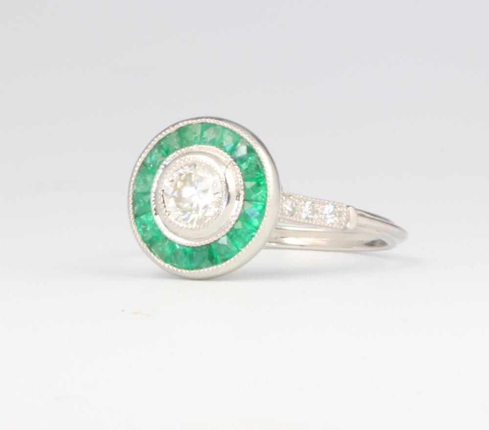 A platinum emerald and diamond Art Deco style ring, the centre brilliant cut diamond approx. 0.