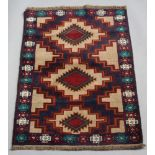 A brown, blue and green ground Belouche rug with 3 stylised medallions to the centre 135cm x 86cm
