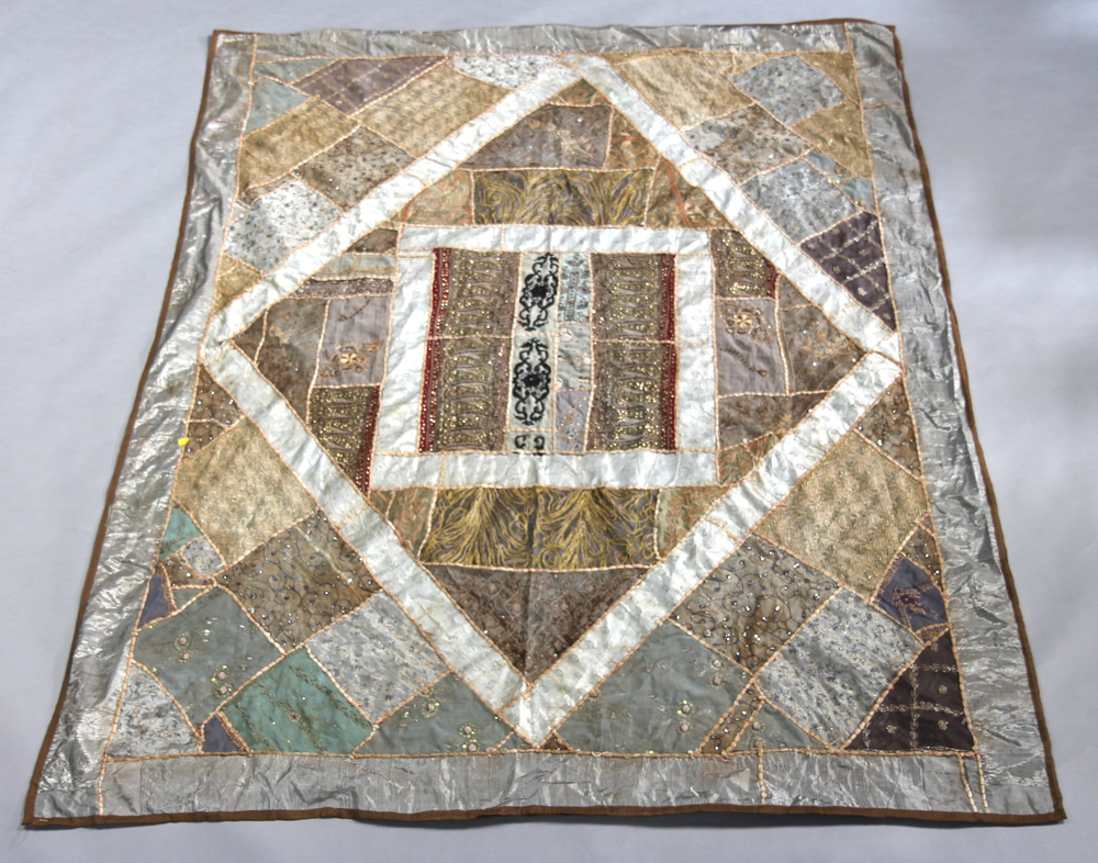 An Eastern embroidered eiderdown with panelled decoration 244cm x 193cm Some staining