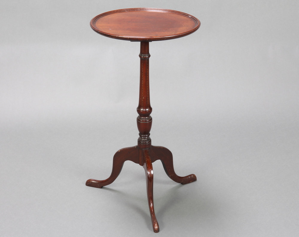 An Edwardian, Georgian style circular mahogany dish top wine table raised on a turned column and