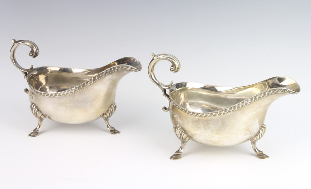 A pair of Edwardian silver sauce boats with S scroll handles on hoof feet London 1905, 780 grams