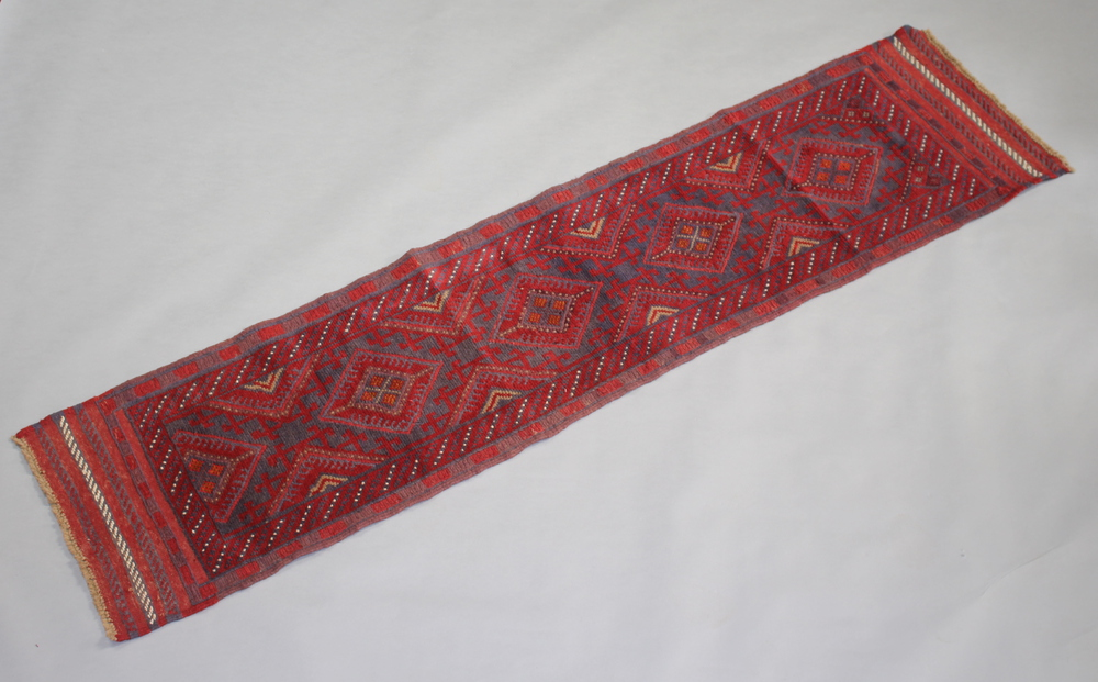 A blue and red ground Meshwani runner with 5 stylised diamond medallions to the centre 245cm x 61cm