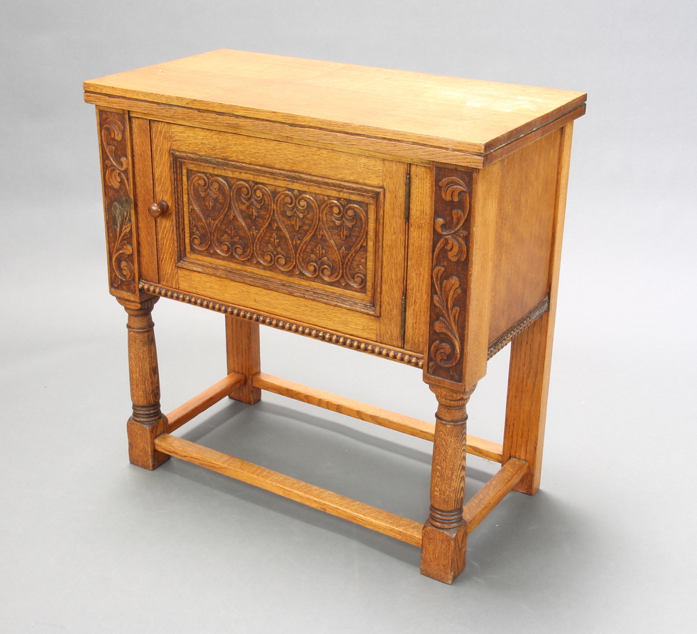A 17th Century style carved oak cabinet fitted a cupboard enclosed by panelled doors, raised on