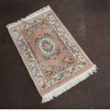 A peach ground and floral patterned Chinese rug 163cm x 92cm Some staining in places