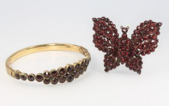 A Victorian gilt garnet set bangle together with a ditto butterfly brooch