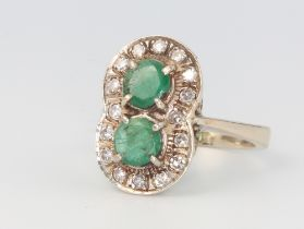 A white metal (marked 750) emerald and diamond double cluster ring, 7 grams, size O 1/2