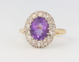 An 18ct yellow gold oval amethyst and diamond cluster ring, 4.4 grams, size M 1/2