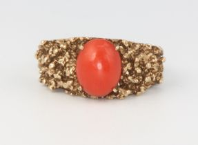 A 9ct yellow gold cabochon coral ring, size M, 6.8 grams