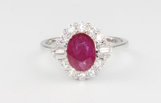 An 18ct white gold oval ruby and diamond ring, the centre stone 1.26ct surrounded by brilliant and