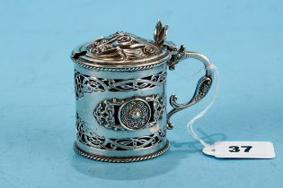 A GEORGE V CIRCULAR IRISH SILVER CELTIC INFLUENCE MUSTARD POT AND COVER, blue glass liner, decorated