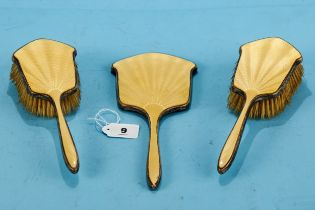 A GEORGE V SILVER AND YELLOW ENAMEL HAND MIRROR and a pair of matching HAIR BRUSHES, maker: WGS LTD,