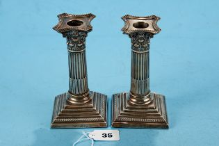 A PAIR OF LATE VICTORIAN CORINTHIAN COLUMN CANDLESTICKS raised on stepped square bases with